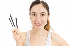 Beautiful woman showing make up pens Stock Image