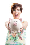Beautiful woman showing a piggybank. Beautiful happy woman holding and showing a piggybank, isolated over a white background Royalty Free Stock Photo