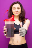Beautiful woman showing a protein shaker with thumbs up gesture. Stock Image