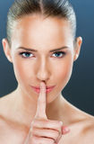 Beautiful woman showing a silence gesture. Close up over a blue background royalty free stock photo
