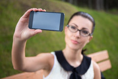 Beautiful woman showing smart phone with blank screen Stock Images