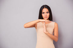 Beautiful woman showing time out sign. Over gray background Stock Images