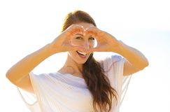 Beautiful woman shows heart shape hands on summer sunny day, oceanside background. Happy beautiful young woman shows heart shape hands on summer, autumn, sunny Stock Image