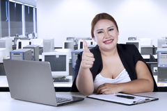 Beautiful woman shows ok sign in office Royalty Free Stock Image