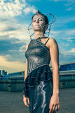 Beautiful woman in a silver dress with crystals on the face Royalty Free Stock Photo
