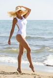 Beautiful woman, simple white swimsui, sun hat at beach Royalty Free Stock Photography