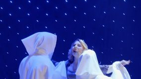 Beautiful woman sing song and dances with strangers in cloaks in theatre. Beautiful woman in long dress sing song on colorful stage in the modern theatre. People stock video
