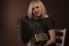 Beautiful woman singing with accordion. Studio shot Stock Photo