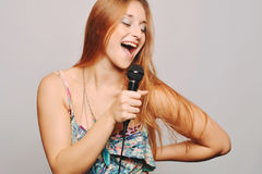 Beautiful woman singing with microphone. Royalty Free Stock Image