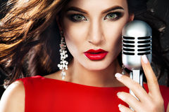 Beautiful woman singing with the microphone. Beautiful Singing Girl. Beauty Woman with Microphone stock photography