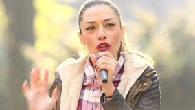 Beautiful woman singing with the microphone stock video