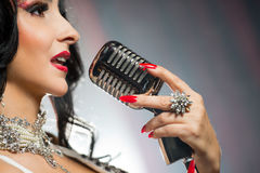 Beautiful woman singing a song with retro microphone Royalty Free Stock Image