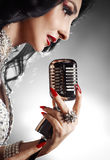Beautiful woman singing a song with retro microphone Stock Image