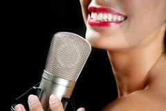 Beautiful woman singing on a vintage microphone Stock Photography