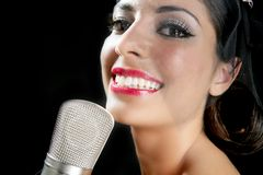 Beautiful woman singing on a vintage microphone Stock Photo