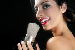 Beautiful woman singing on a vintage microphone Stock Photos