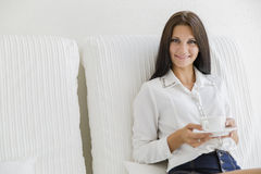 Beautiful woman sipping coffee from a white cup Royalty Free Stock Image
