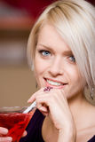 Beautiful woman sipping a martini. Beautiful blue eyed blond woman sipping a martini cocktail through a straw, closeup head portrait Stock Image