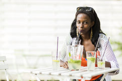 Beautiful woman sipping through a straw outdoors Royalty Free Stock Image
