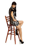 Beautiful woman sit on high wooden chair. Royalty Free Stock Photo