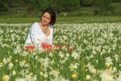 Beautiful woman sit in white flowers field. Young happy woman in a white daffodil flowers field Stock Photos