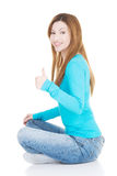 Beautiful woman sitiing and showing OK. Royalty Free Stock Photo
