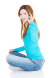 Beautiful woman sitiing and showing OK. Stock Photo