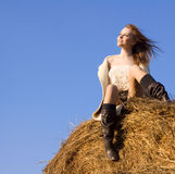 Beautiful woman siting on haystack Royalty Free Stock Photography