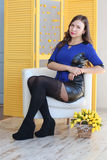 Beautiful woman sits in armchair Stock Photos