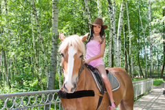 Beautiful woman sits astride on a horse Royalty Free Stock Images