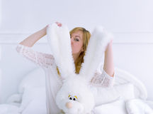 The beautiful woman sits in a bed with toy. Royalty Free Stock Images