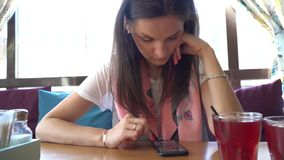Beautiful woman sits in the cafe uses smartphone. Beautiful woman sits in the cafe uses her smartphone stock video footage