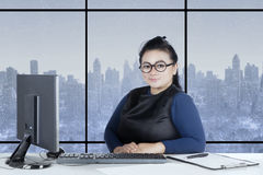Beautiful woman sits with computer on desk Stock Photos