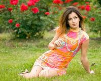 Beautiful woman sits on a grass Royalty Free Stock Photography
