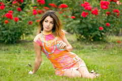 Beautiful woman sits on a grass Stock Photo