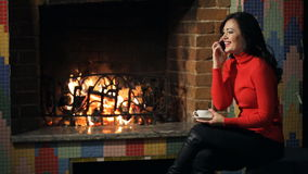 Beautiful woman sits near fireplace, talks on mobile phone. stock video footage