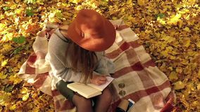 Beautiful woman sits on a plaid in the autumn forest, makes notes in a notebook and enjoys good weather. Slow motion. Beautiful woman sits on a plaid in the stock video