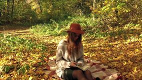 Beautiful woman sits on a plaid in the autumn forest, makes notes in a notebook and enjoys good weather. Slow motion. Beautiful woman sits on a plaid in the stock footage