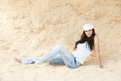 Beautiful woman sits sand Royalty Free Stock Image