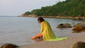 Beautiful woman sits on stone on sea beach