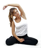 A beautiful woman sits and stretches. A beautiful woman sits and stretches before exercise, set against a white background Stock Image
