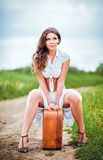 Beautiful woman sits on a suitcase near rural road Stock Photos