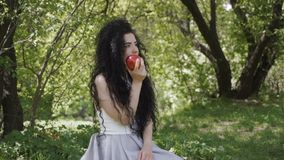 Beautiful brunette sit in summer garden and eat red apple. Beautiful woman sits in summer garden and eat red apple. Charming brunette enjoys of fruit and smiling stock footage