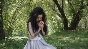 Beautiful woman in blue dress enjoy a smell of fresh red apple. Beautiful woman sits in summer garden and enjoy a smell of fresh red apple. Charming brunette is stock video