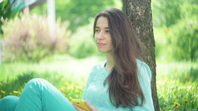 Beautiful woman sits under a tree with a smartphone in a summer park.  stock footage