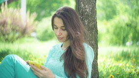 Beautiful woman sits under a tree with a smartphone in a summer park.  stock video