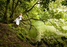 Beautiful woman sits in white long dress on branch of a tree, next to a lake. Green landscape in Azores island, Portugal. Hidden lake, tranquile scene, beautiful Stock Photography