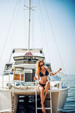 Beautiful woman sits on white yacht in the sea Royalty Free Stock Photography