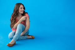 Beautiful woman sitting against blue background Stock Image