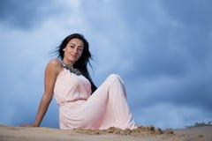 Beautiful woman sitting alone on a sand dune Stock Photo